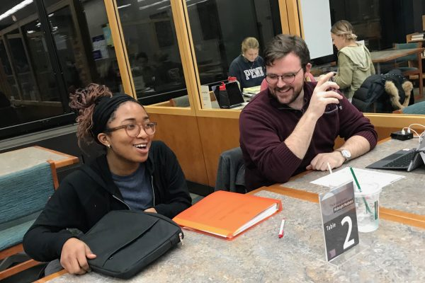 A Writing Center tutor works one-on-one with a student at a workshop event