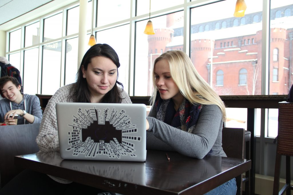 Two women sit at a table and look at a laptop together.