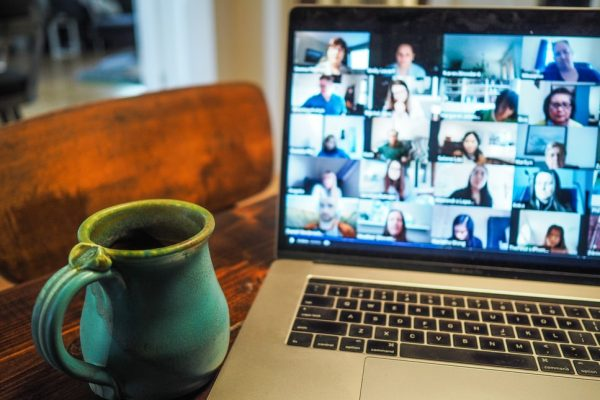 Photo of coffee mug next to a computer screen with many participants